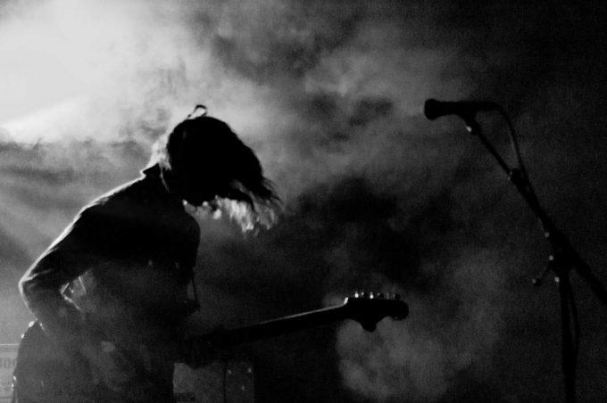 Ein Gitarrist im Bühnennebel