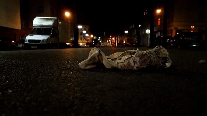 Ein alter Fetzen liegt auf einer dunklen Straße.