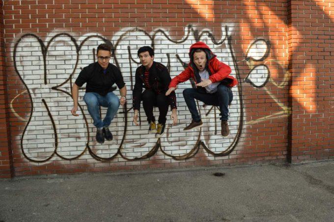 """Die 3 """"Horny Women"""" Bandmitglieder hüpfen vor einer Mauer in die Luft."""