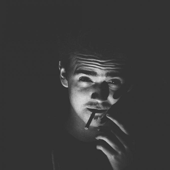 Klaus Zwinger raucht eine Zigarette vor einem schwarzen Hintergrund